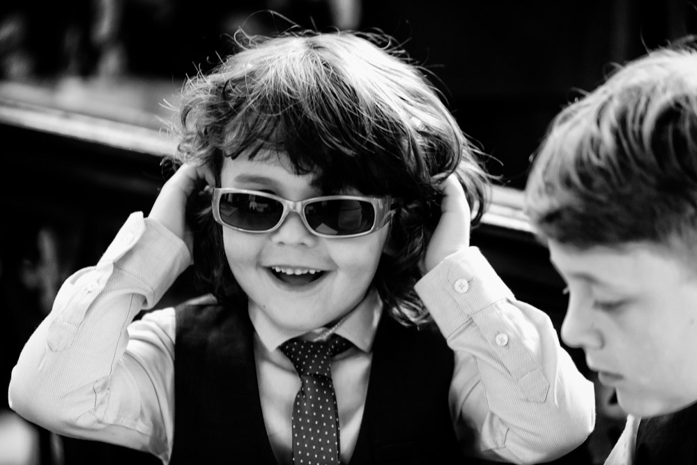 A small boy puts on sunglasses