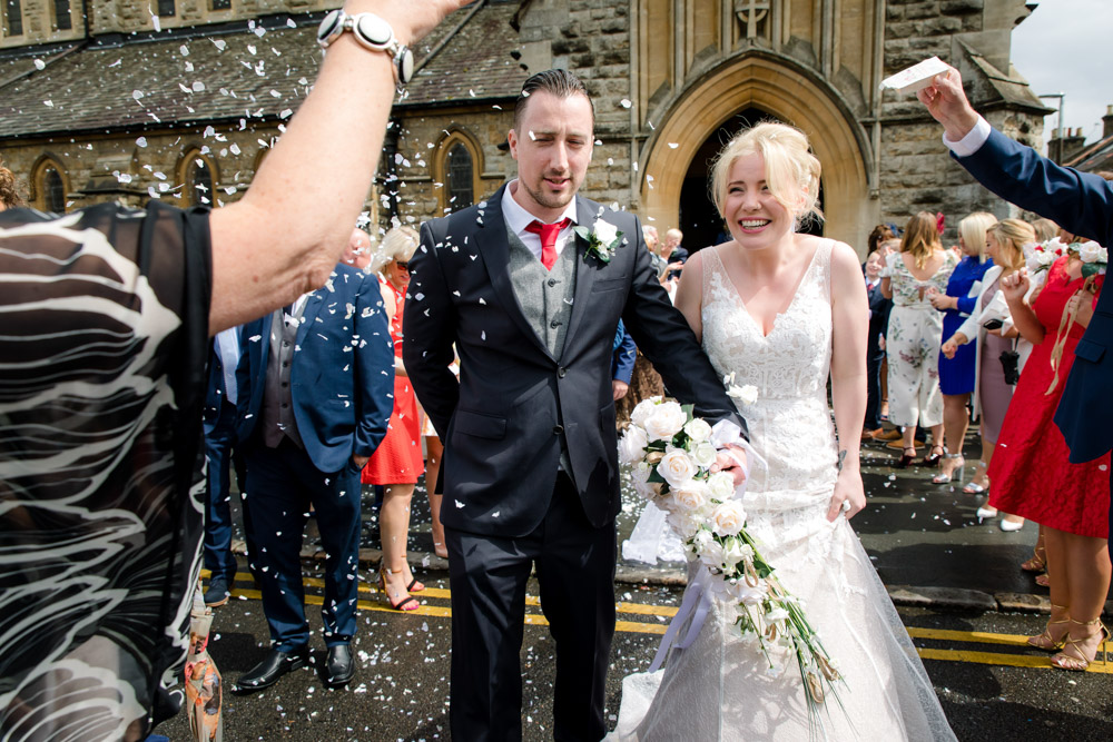 Guests throw confetti outside a church in watford