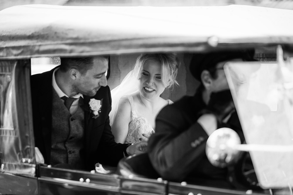 The bride and groom in the back of the wedding car together
