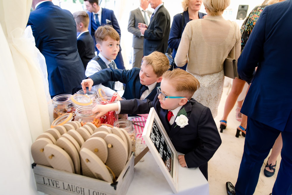 Young boys pick up sweets from the sweet table at a wedding reception