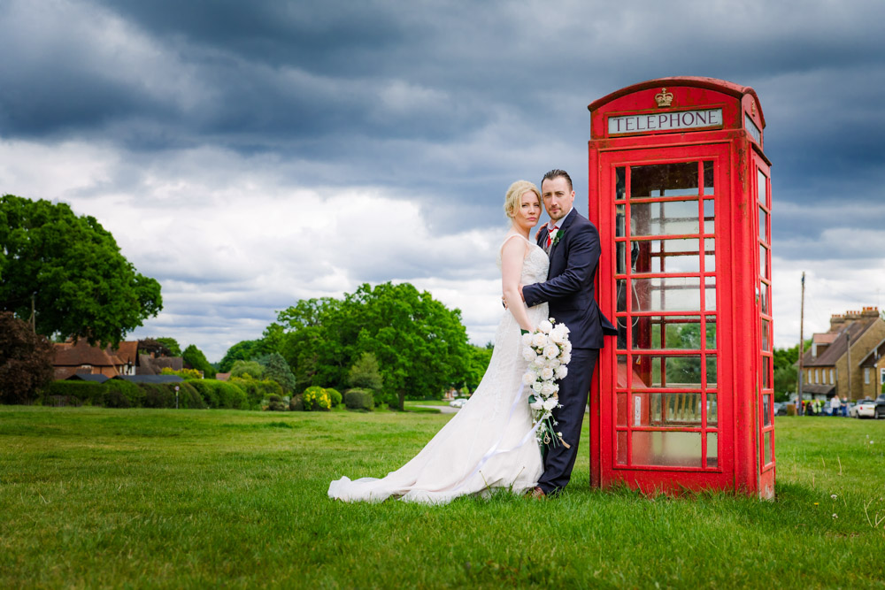 The bride and groom pose next to a red phone box in Hertfordshire