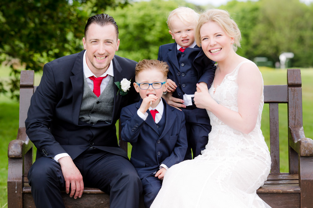 The bride and groom with their children sit on a bench