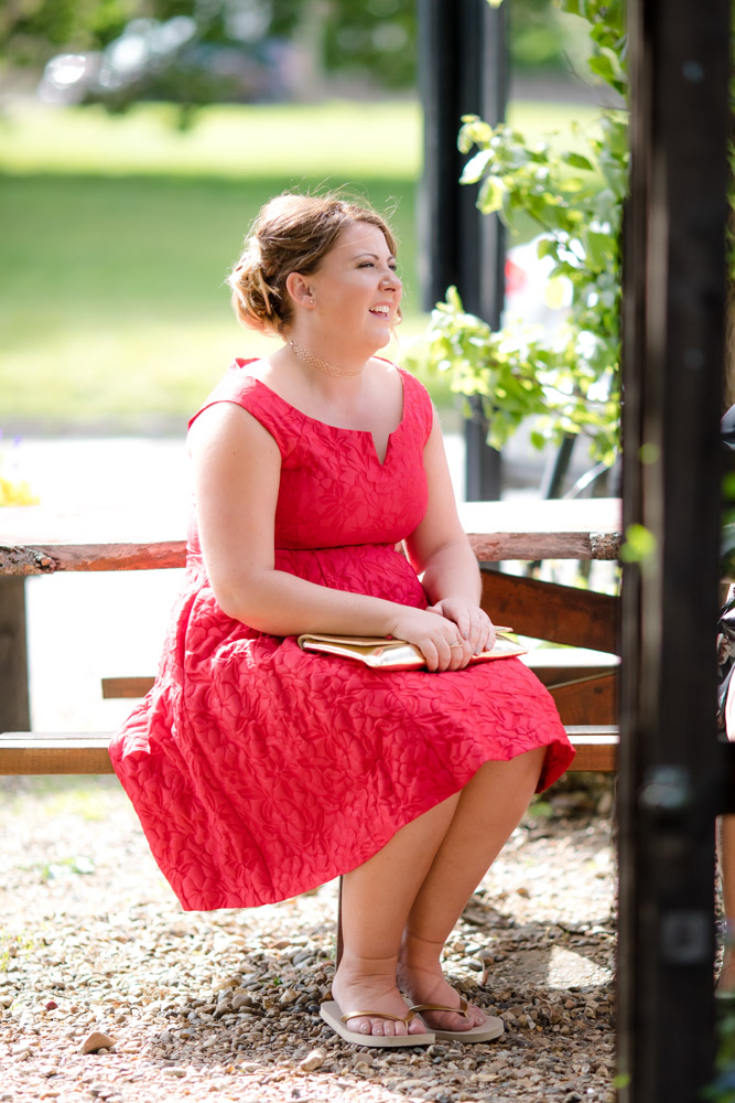 A bridesmaid sits on a bench