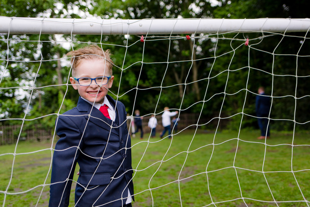 A page boy smiles through the goal at a wedding reception