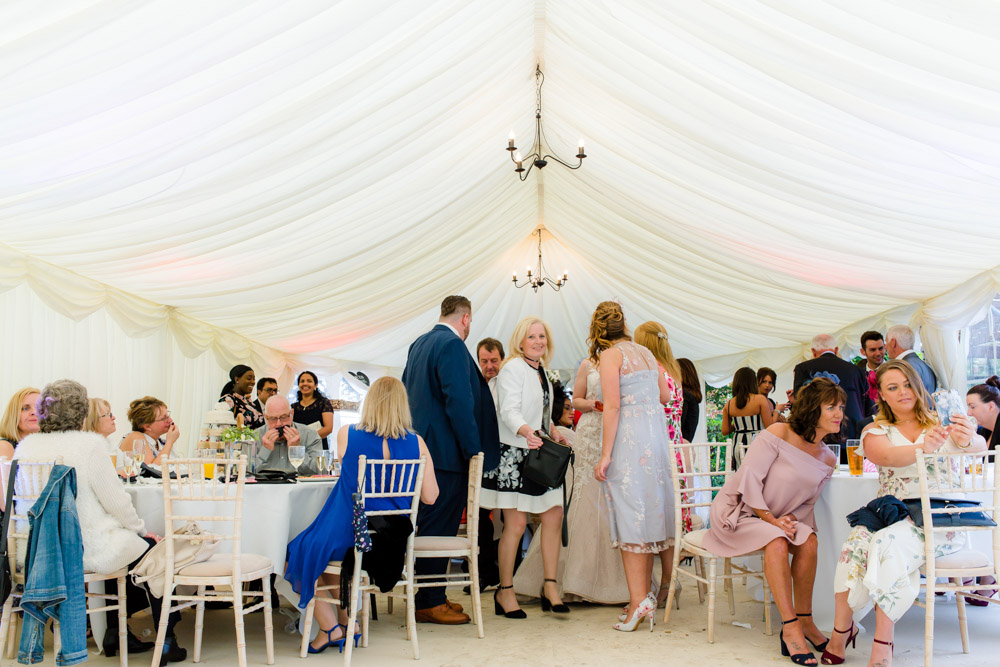 Guests gather in the marquee at a wedding in sarratt