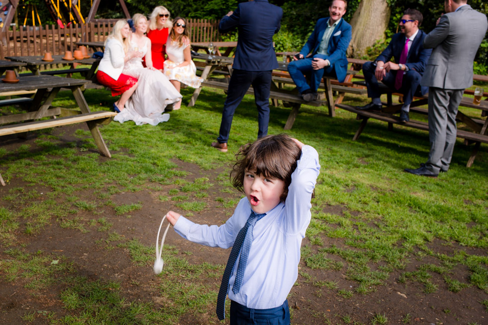 A boy holds his head during a wedding reception