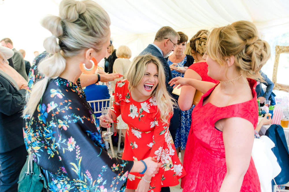 Guests laugh at a wedding reception
