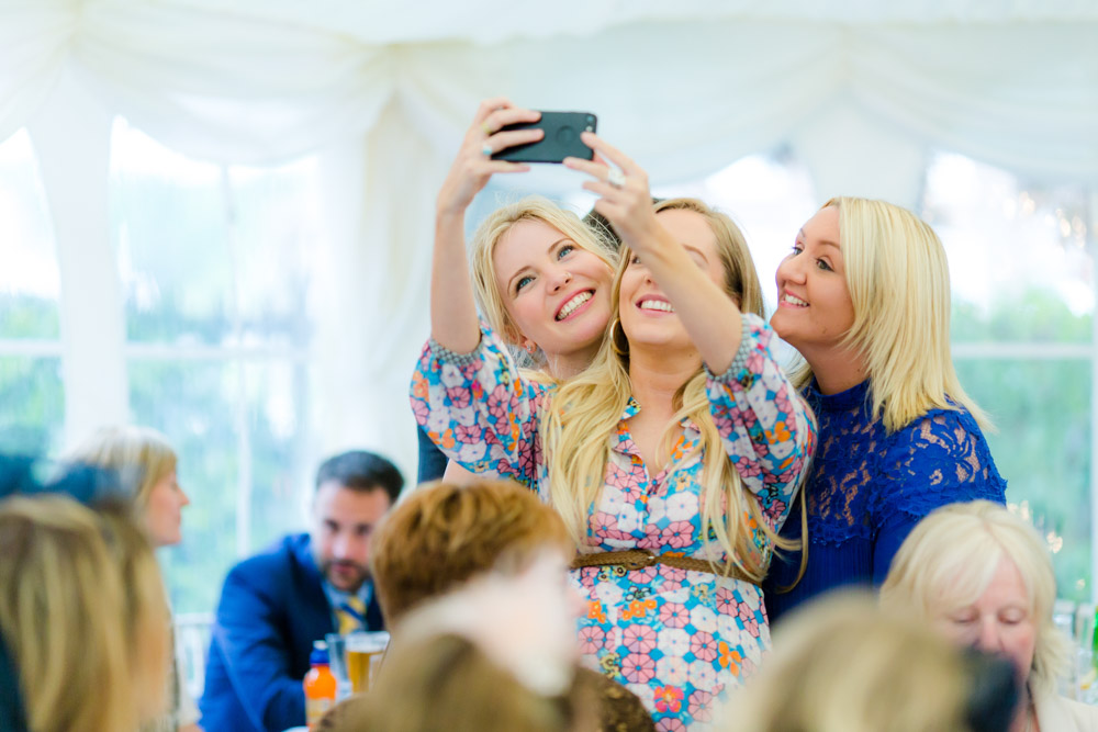 Guests smile into a camera at a wedding reception