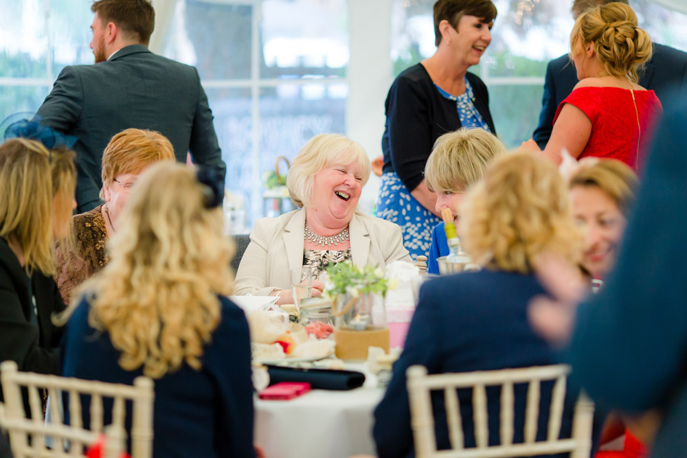Female guests laugh around a table at a wedding reception