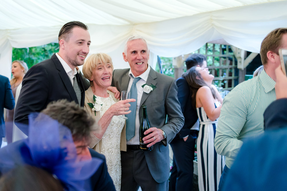 The groom poses with his parents during the wedding reception