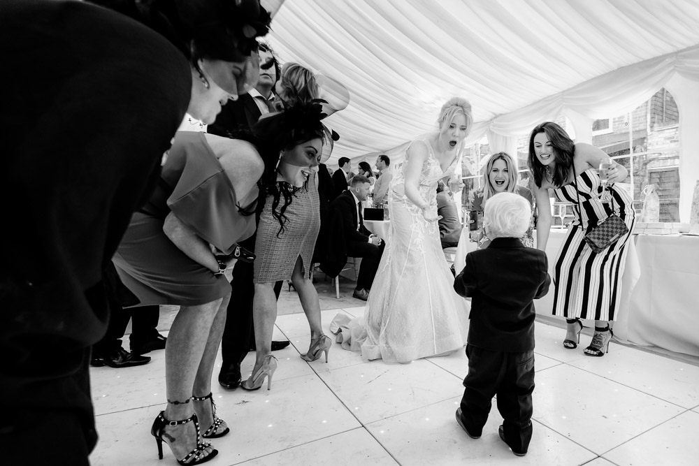 The ladies gather round a small boy at a wedding