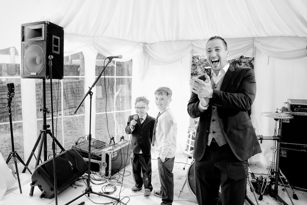 The groom laughs as the page boy makes a speech