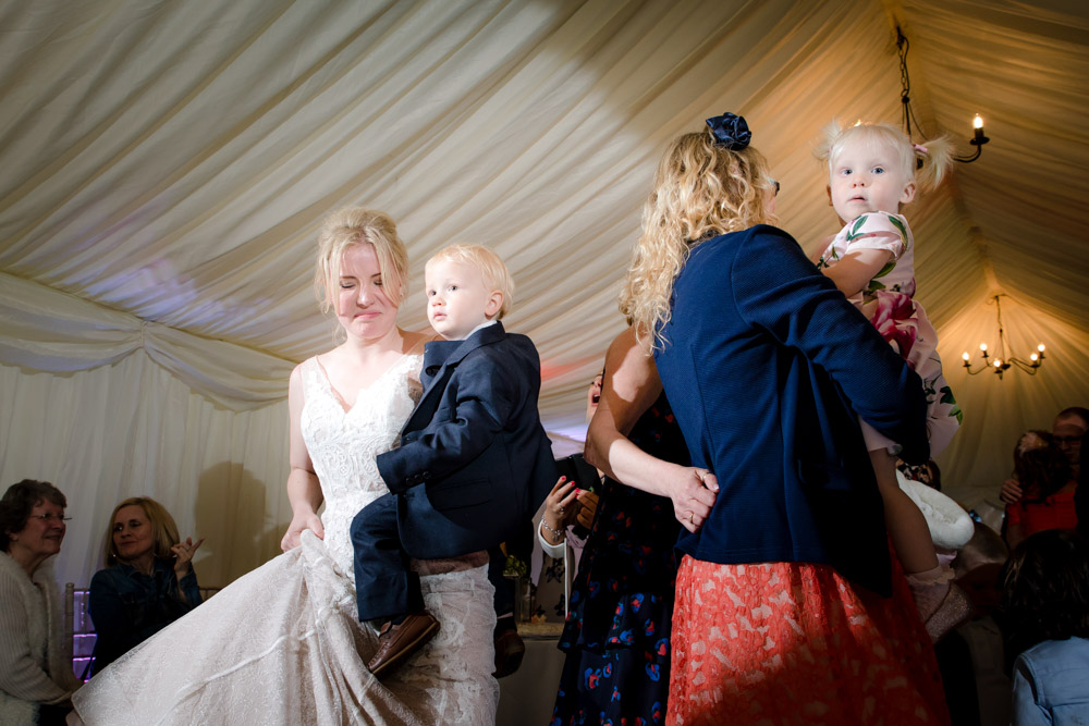 Guests hold young children at a wedding