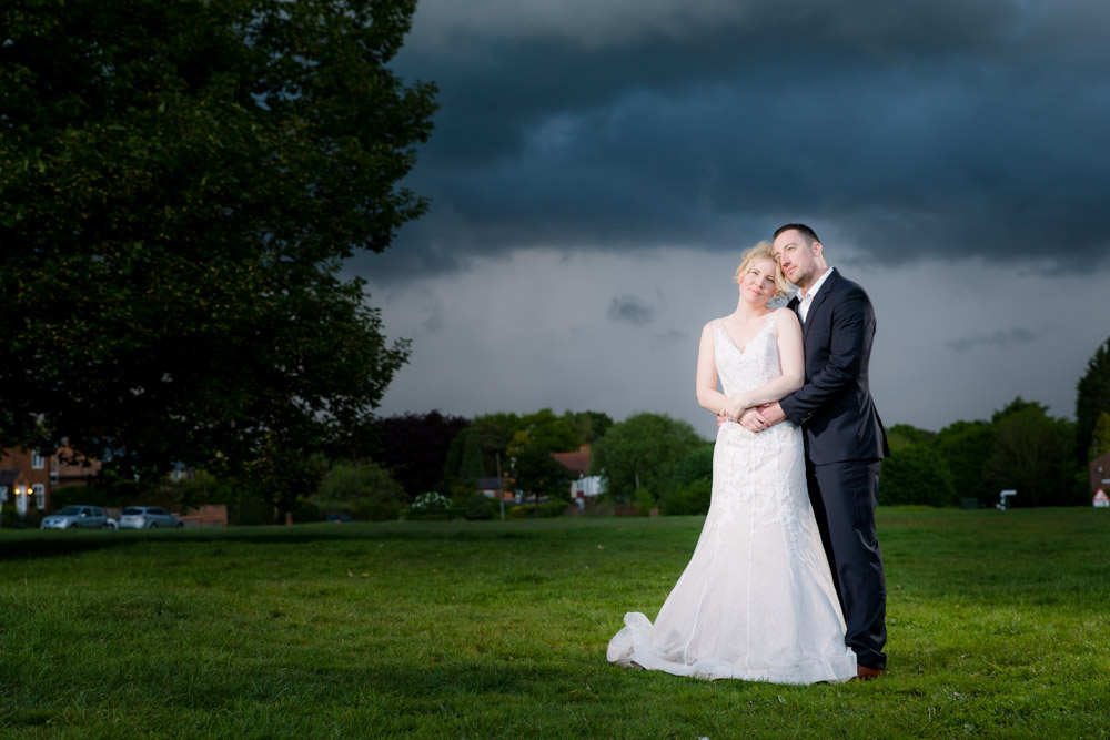 The bride and groom with a moody sky behind
