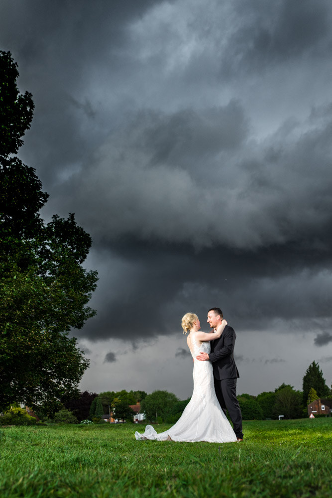 The bride and groom embrace under a big cloud